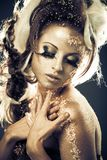 Golden lady. Vogue style portrait of a woman with gold-silver bodyart and makeup Stock Images