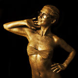 Golden lady. Young woman with golden skin royalty free stock image