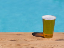 Golden lager or beer in disposable plastic cup. Golden beer, ale or lager a plastic disposable cup for party on wooden table by swimming pool Stock Photos