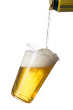 Golden lager or beer in disposable plastic cup. Golden beer, ale or lager in a tilting plastic disposable cup or glass with beer being poured from can and stock photo