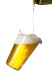 Golden lager or beer in disposable plastic cup. Golden beer, ale or lager in a tilting plastic disposable cup or glass with beer being poured from can and Stock Image