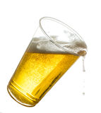 Golden lager or beer in disposable plastic cup. Golden beer, ale or lager in a tilting plastic disposable cup or glass with beer spilling over edge of pint glass stock image