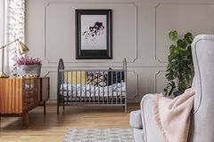 Golden lamp and heather in patterned pot on the vintage cabinet in grey baby room interior with crib and armchair. Concept stock image