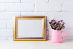 Golden landscape frame mockup with purple flowers in pink rusti. Golden landscape frame mockup with purple field flowers in polka dot pink rustic pitcher vase stock photos