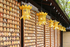 Golden lanterns hanging in front of mirror-shaped wooden preyer Royalty Free Stock Photos