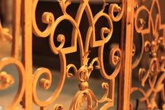 Golden lattice forged fence. Golden iron lattice gates decorative with leaves royalty free stock photo