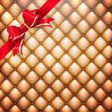 Golden leather  with red. EPS 10. Illustration of golden realistic upholstery leather pattern background with red gift bow. EPS 10 vector file included Stock Photography