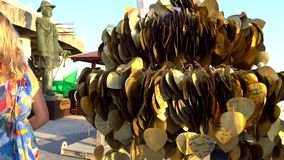 Golden leaves hanging from trees on a seated Buddha statue. There`s a wish written on the back. Entrance to the big Buddha temple. Fulfillment of dreams stock video footage
