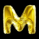 Golden letter M made of inflatable balloon isolated on black background. 3d rendering stock illustration