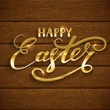Golden lettering Happy Easter on brown wooden background Stock Photo