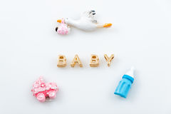 Golden letters. Word baby on white with tiny toys. Pacifier, pram and bird carrying a newborn. Stock Photography