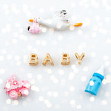 Golden letters. Word baby on white with tiny toys. Pacifier, pram and bird carrying a newborn. Royalty Free Stock Photo
