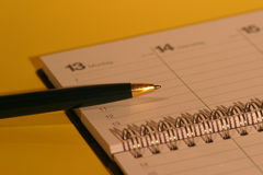 Golden light. Macro of a calendar and a biro stock photos
