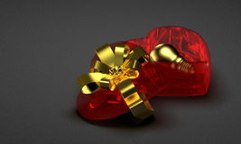 Golden light bulb in red glass heart-shaped box Royalty Free Stock Image