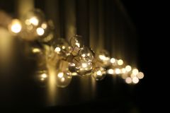 Golden light bulbs on the night dark background. City lights. Bokeh soft abstract background. Bokeh - Image royalty free stock photo