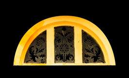 Golden light through carved window on black isolated background Stock Images