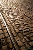 Golden light railroad. Old rail trolley on the street with stone parallelepiped stone paving Stock Images
