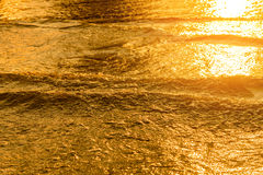 Golden light reflecting off a water wave at the sea and sand on sunset. Pure Gold Tone Stock Photos