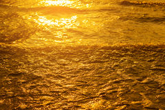 Golden light reflecting off a water wave at the sea and sand on sunset. Pure Gold Tone Royalty Free Stock Photo