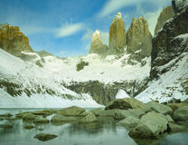 Golden light shining on towers of Torres del Paine Chile. The granite towers at base torres under special conditions, covered in snow at national park Torres del stock photography