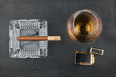 Golden lighter with a glass of alcohol and cigar lying on a black skin Royalty Free Stock Photos