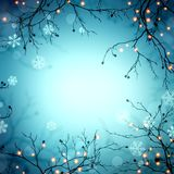 Golden lights on branches frame. Festive garland on trees in forest. Snowflakes and bokeh blurred empty blue background. Winter ma. Stylish image for a variety Royalty Free Stock Image