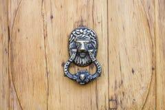 Golden lion door knocker in a wooden door. Stock Photo