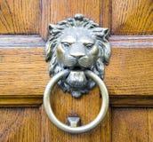 Golden lion head knocker on an old wooden door Royalty Free Stock Photos