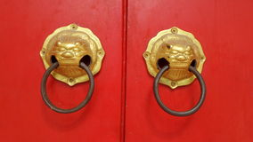 Golden lion knob on red door Royalty Free Stock Images