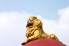 Golden lion statue. Low angle view of golden lion statue with blue sky and cloudscape background Royalty Free Stock Images