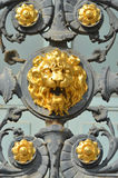 A golden lion on a wrought-iron gate. The face of a lion covered in gold leaf. It is on a stylized wrought-iron gate Royalty Free Stock Photos
