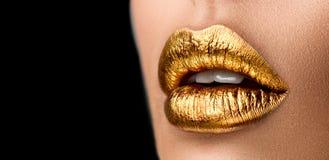 Golden lipstick closeup. Metal gold lips. Beautiful makeup. Sexy lips, bright paint on beautiful model girl`s mouth, close-up