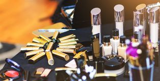 Golden lipstick collection. Big set of cosmetic products lie on table. Real make up kit of professional beautician. royalty free stock photo