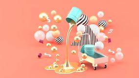Golden liquid paints spouting from blue can among the colorful balls on the pink background. royalty free stock image