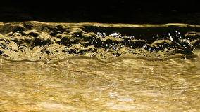 Golden liquid wave Stock Images