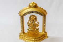 Golden lord Ganesha Hindu idol designed in a stage in a white backdrop. Macro with extremely shallow depth of field Stock Photos