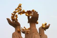 Golden lotus flowers and hands. Sculpture of hands holding golden lotus flowers in sky Stock Photos