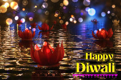 Golden lotus shaped diya floating on river in Diwali background Stock Images