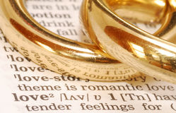 Golden Love. The word 'Love' listed in a dictionary with two gold rings next to it Stock Photo