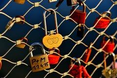 Golden love lock on the bridge. Golden love locks on Makartsteg bridge crosses the Salzach River Stock Photos