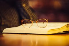 Golden luxury glasses on book lying on library table. royalty free stock images