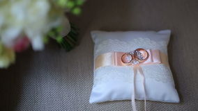 Golden luxury wedding rings on small white cushion with pink ribbon.  stock video footage