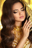 Golden makeup. Elegant brunette woman. Fashion jewelry. Wavy hai Stock Photos