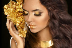Golden makeup eyes closeup. Beautiful young woman in gold with f Stock Images