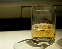 Golden malt whiskey served with ice on a table. Served in a first class cabin of an airplane Stock Images