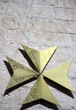 Golden maltese cross. Maltese Cross in a palace in Malta. Wall background Stock Images