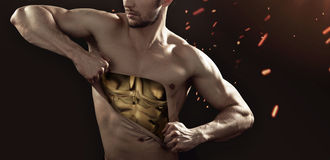 Golden man tearing up his chest Royalty Free Stock Photography