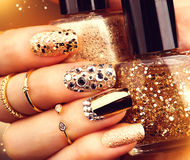 Golden manicure with gems and sparkles. Bottle of nailpolish, trendy accessories Stock Photography