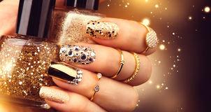 Free Golden Manicure With Gems And Sparkles. Bottle Of Nailpolish, Trendy Accessories Stock Images - 65575354