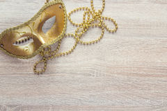 Golden Mardi Gras masks and beads on a wooden background. Stock Image